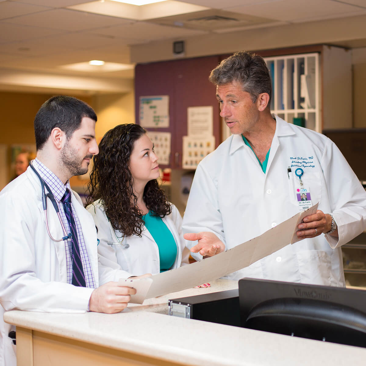 Two physician trainees listen to their supervising physician in a hospital hallway.